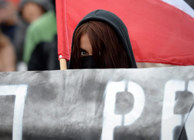 A protester peeks out from behind of a banner as supporters of anti-immigrant activists and nationalists march to protest against the Polish governments decision to accept migrants from Syria and North Africa, in Warsaw, Poland, September12, 2015. (Photo by Jacek Turczyk/EPA)
