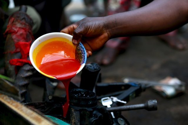 Chief Priest, Gbenga Saala pours palm oil on car keys and other metals during an annual prayer and sacrifice of the iron god Ogun in Abuja, Nigeria, June 23, 2015. (Photo by Afolabi Sotunde/Reuters)