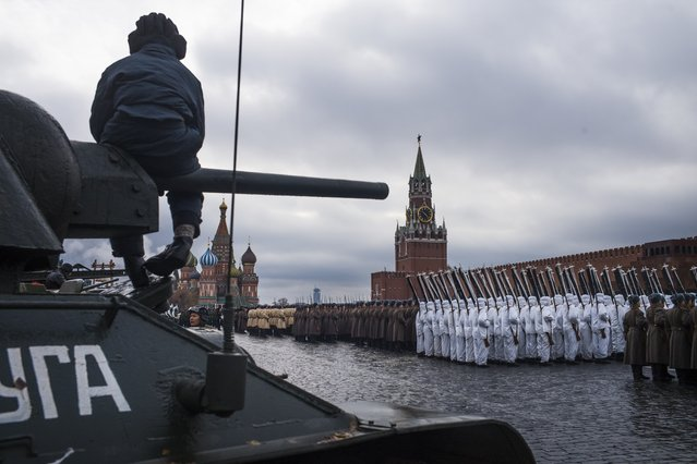 A volunteer sits atop of a legendary Soviet era T-34 tank during a rehearsal of the historical parade in Red Square, in Moscow, Russia, Sunday, November 5, 2017. (Photo by Alexander Zemlianichenko/AP Photo)