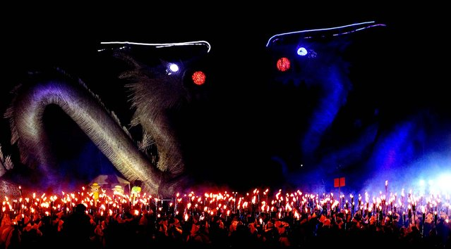 People gather with torches to celebrate the Jipyongsun (horizon) Festival, to experience the agricultural lifestyle in Gimje, South Korea, October 13, 2012. (Photo by Ahn Young-joon/Associated Press)