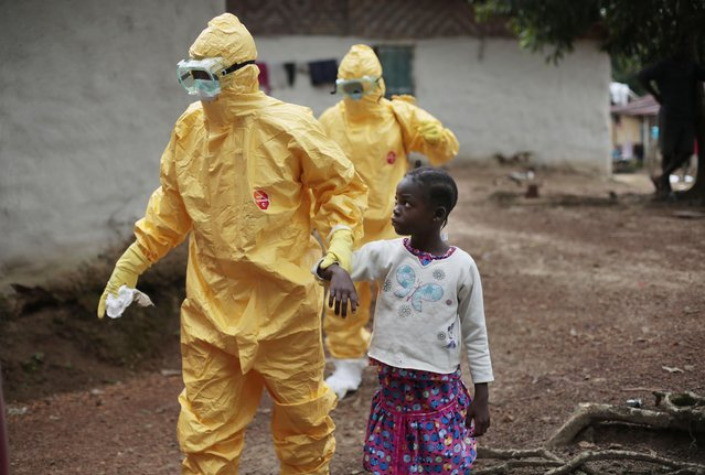 Nowa Paye, 9, is taken to an ambulance after showing signs of the Ebola infection in the village of Freeman Reserve, about 30 miles north of Monrovia, Liberia,Tuesday September 30, 2014. Three members of District 13 ambulance service traveled to the village to pickup six suspected Ebola sufferers that had been quarantined by villagers. (Photo by Jerome Delay/AP Photo)