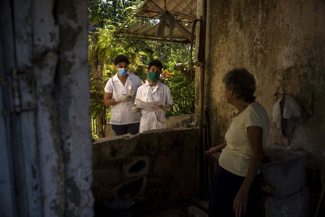 Cuban medical students Hector Manuel Batista, center right, and Ricardo Delgado talk to a woman at her home as they look for possible cases of the new coronavirus in rural areas in San Jose de las Lajas, Cuba, Thursday, April 30, 2020. (Photo by Ramon Espinosa/AP Photo)