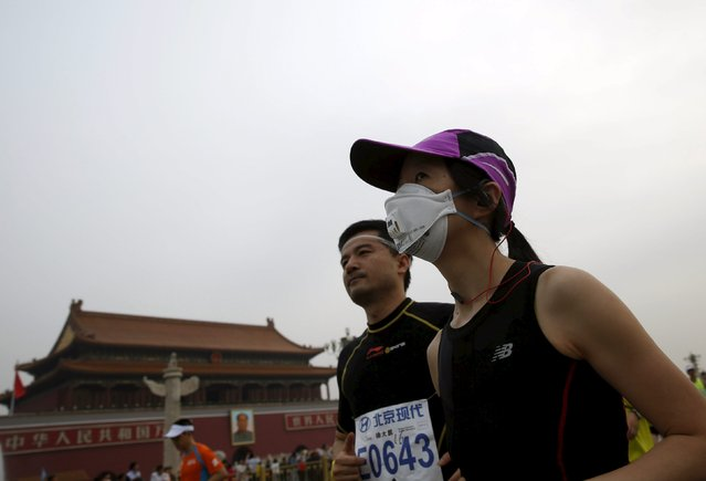 A participant, wearing a mask, runs past the Tiananmen gate during the Beijing International Marathon in Beijing, China, September 20, 2015. (Photo by Kim Kyung-Hoon/Reuters)