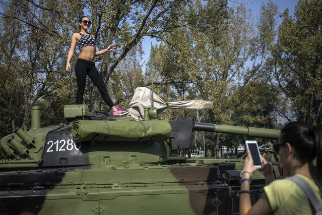 A woman poses on a Serbian army tank during preparations for a military parade in Belgrade October 13, 2014. Serbia is preparing to mark the upcoming 70th anniversary of the liberation of Belgrade in WWII with its first military parade in 29 years. (Photo by Marko Djurica/Reuters)