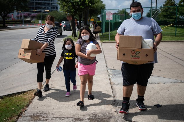 Members of the Rodriguez family carry groceries distributed by the Houston Food Bank for residents affected by the economic fallout caused by the coronavirus pandemic in Houston, Texas, July 18, 2020. (Photo by Adrees Latif/Reuters)