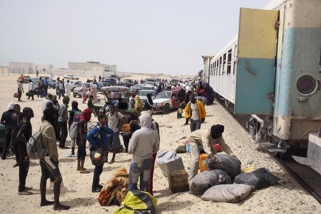Passengers on a SNIM train carrying iron ore and mine workers arrive in Nouadhibou June 25, 2014. (Photo by Joe Penney/Reuters)