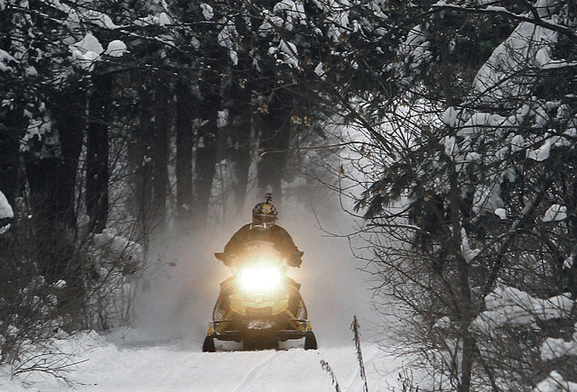 In this December 31, 2012 file photo, a snowmobile travels a newly-groomed trail in East Montpelier, Vt. With plenty of fresh snow covering much of northern New England, the 2017 winter snowmobile season is off to a good start. (Photo by Toby Talbot/AP Photo)