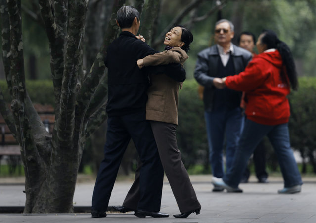 A Chinese woman enjoys a social dance at Ritan Park in Beijing, China Thursday, October 30, 2014. Levels of self-reported well-being in fast-growing nations like Indonesia, China and Malaysia now rival those in US, Germany and the United Kingdom, rich nations which have long topped the happiness charts, according to a Pew Research Center global survey released Friday that it showed how national income was closely linked to personal life satisfaction. (Photo by Andy Wong/AP Photo)