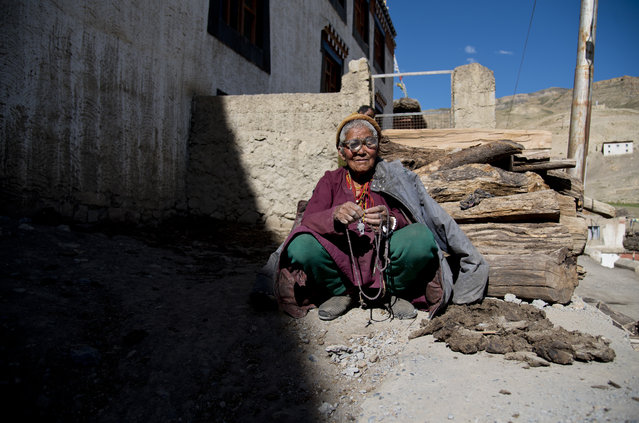 In this August 16, 2016, photo, an elderly woman sits in front of her house in the village of Kibber, in Spiti Valley, India. (Photo by Thomas Cytrynowicz/AP Photo)
