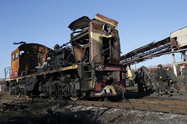 "Miners walk past a destroyed train at coal mine number 22 ""Kommunar"" in the village of Nizhnyaya Krynka, east from Donetsk, November 6, 2014. The mine, which was previously controlled by the Ukrainian security forces and fighters of the Aidar battalion of the National Guard, was damaged in fighting between Ukraine's troops and pro-Russian rebels, and has since been restored. (Photo by Maxim Zmeyev/Reuters)"