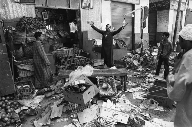 Shopkeeper in the Egyptian city of Asyut raises his arms in exasperation on October 9, 1981, after he said police looted his wares in the wake of a 24-hours gun battle between police, aided by the army, and Islamic extremists. (Photo by AP Photo/JJ)