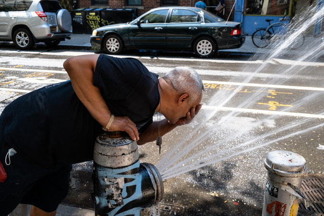 A man washes his face in an open fire hydrant on a hot day in the East Village, New York, NY. on August 24, 2020. (Photo by Stephen Yang/The New York Post)