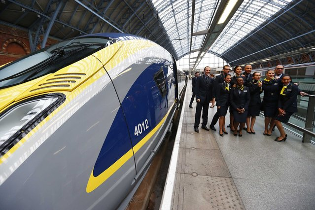 Eurostar employees pose as a colleague (unseen) takes a photograph of them next to their new Siemens e320 train at St Pancras station in central London, November 13, 2014. (Photo by Andrew Winning/Reuters)