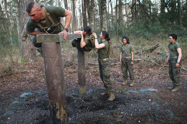 Male and female Marines climb an obstacle on the Endurance Course during Marine Combat Training (MCT) on February 20, 2013 at Camp Lejeune, North Carolina.  Since 1988 all non-infantry enlisted male Marines have been required to complete 29 days of basic combat skills training at MCT after graduating from boot camp. MCT has been required for all enlisted female Marines since 1997. About six percent of enlisted Marines are female.  (Photo by Scott Olson)