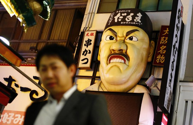 A man walks past an bas-relief advertising a Japanese restaurant in the Dotonbori amusement district of Osaka, western Japan November 19, 2014. (Photo by Thomas Peter/Reuters)