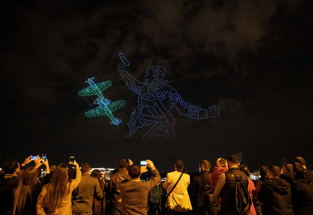 """People watch a light show """"Peaceful sky-drone show"""" dedicated to the 75th anniversary of the end of World War II in the center of St. Petersburg, Russia, 03 September 2020. Around 2000 glowing drones show figures reaching 600 meters in their size. (Photo by Anatoly Maltsev/EPA/EFE/Rex Features/Shutterstock)"""