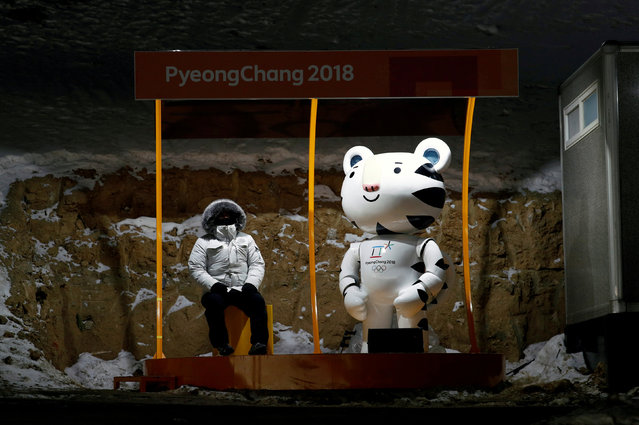A fan sits next to Soohorang, the Olympic mascot, at the Olympic Sliding Centre in Pyeongchang, South Korea on February 12, 2018. (Photo by Edgar Su/Reuters)