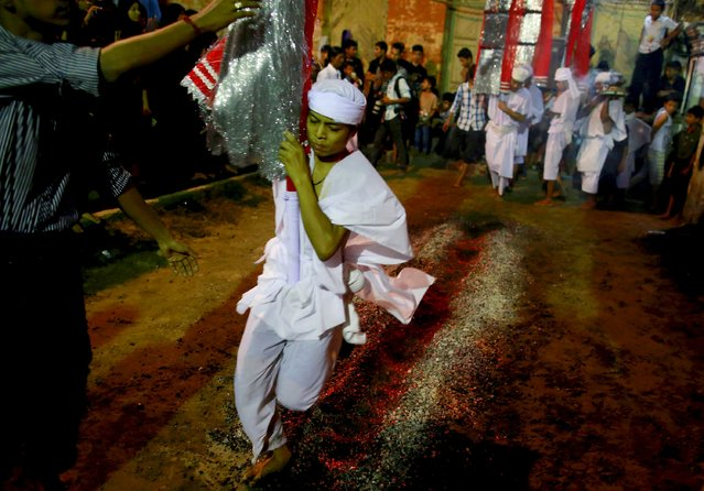 A Shi'ite Muslim walks on hot coals at a ceremony during the Ashura festival at a mosque in central Yangon October 21, 2015. Ashura is the most important day in the Shi'ite calendar, which commemorates the death of Imam Hussein, grandson of the Prophet Mohammad, in the 7th century battle of Kerbala. (Photo by Soe Zeya Tun/Reuters)