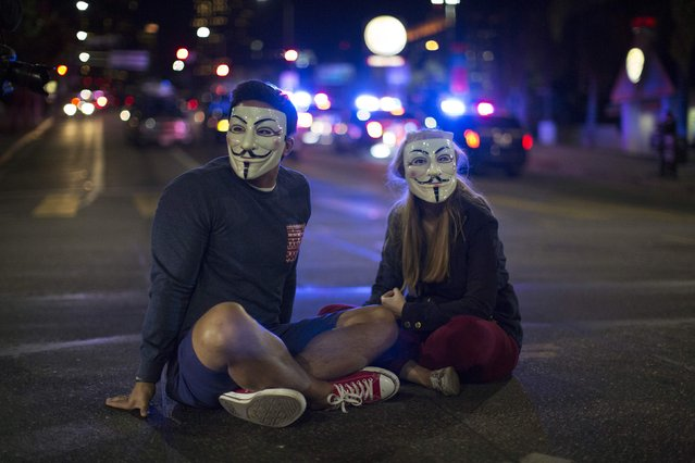 Activists Tim Marchant and Morgan Bischoff wear Guy Fawkes masks while sitting on a street in Los Angeles, California, following Monday's grand jury decision in the shooting of Michael Brown in Ferguson, Missouri, November 25, 2014. U.S. President Barack Obama said on Tuesday anyone who destroys property in rioting against a Missouri grand jury's decision should be prosecuted, urging Americans upset by the court to work together to improve race relations. (Photo by Mario Anzuoni/Reuters)