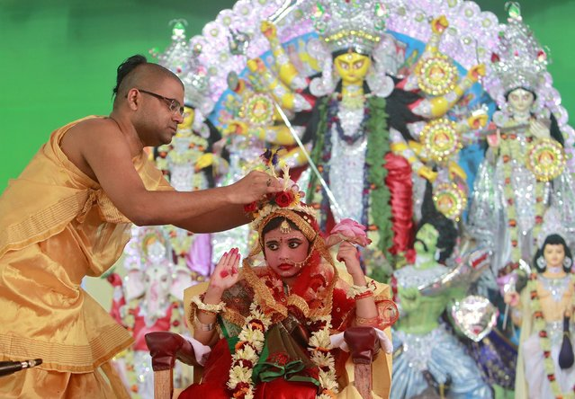 A Hindu priest adjusts the headgear of Nilanjana Chakraborty, a five-year old girl dressed as a Kumari, during the religious festival of Durga Puja in Agartala, India, October 21, 2015. Kumari is a young virgin girl who is worshipped as part of the Durga Puja rituals. The festival is the biggest religious event for Bengali Hindus. Hindus believe that the goddess Durga symbolises power and the triumph of good over evil. (Photo by Jayanta Dey/Reuters)