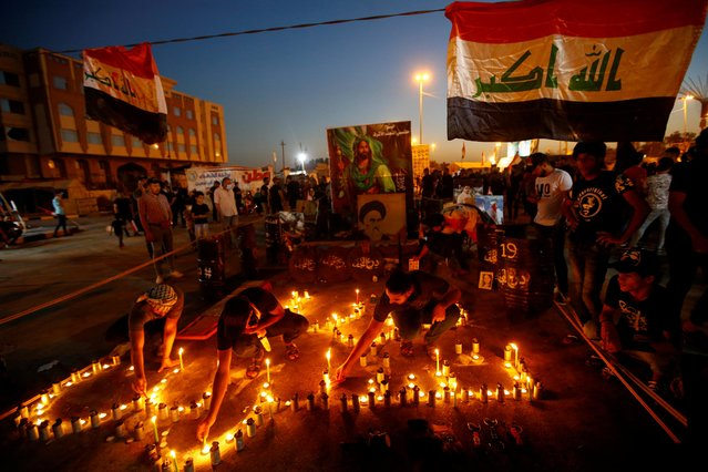 Men light candles as Iraqi demonstrators gather to mark the first anniversary of the anti-government protests, in Najaf, Iraq on October 1, 2020. (Photo by Alaa Al-Marjani/Reuters)