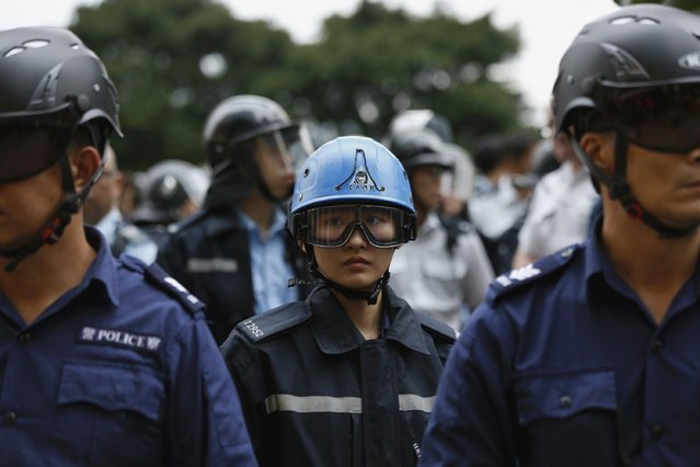 A riot policewoman stands in between her colleagues during clashes with pro-democracy protesters outside the government headquarters in Hong Kong December 1, 2014. (Photo by Bobby Yip/Reuters)