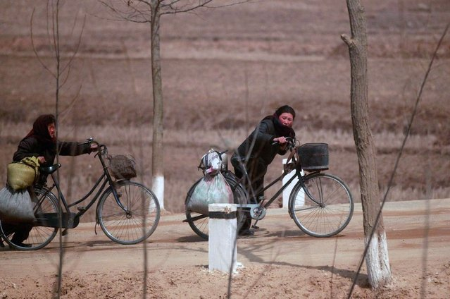 Villagers push their bicycles on a road between fields northwest of Pyongyang, on April 8, 2012. (Photo by Bobby Yip/Reuters)