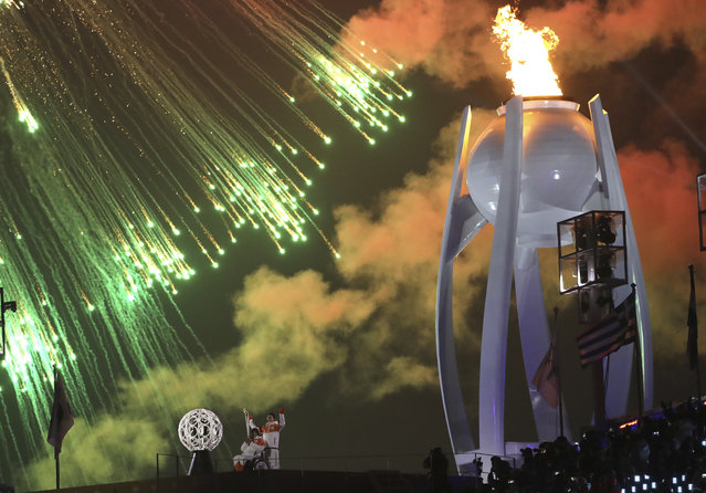 Fireworks explode as the Olympic cauldron is lit during opening ceremony of the 2018 Winter Paralympics in Pyeongchang, South Korea, Friday, March 9, 2018. (Photo by Ng Han Guan/AP Photo)