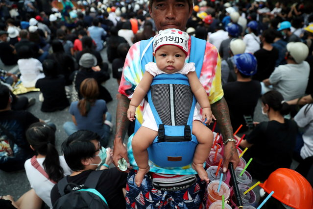 A vendor carrying a baby sells cool drinks during a protest in Bangkok, Thailand on October 26, 2020. (Photo by Soe Zeya Tun/Reuters)