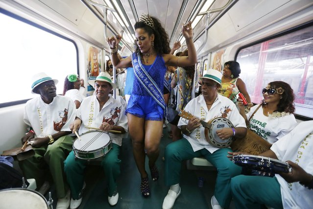 "A reveller dances among musicians inside the ""Trem do Samba"" (Train of Samba) in Rio de Janeiro, December 6, 2014. The Train of Samba, one of the events which mark National Samba Day, sees thousands for people flocking to the Oswaldo Cruz neighbourhood to remember a tradition which Samba composer Paulo da Portela started in the 1920s. (Photo by Pilar Olivares/Reuters)"