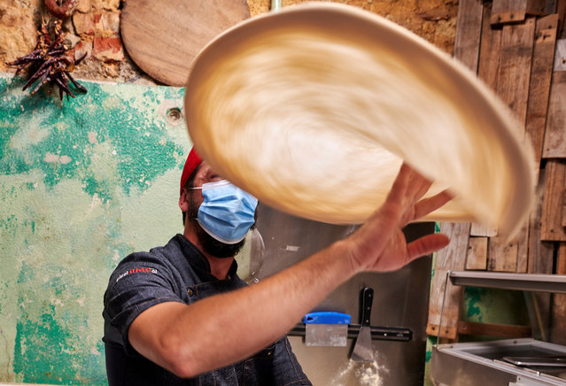 "Chef Roberto Mezzapelle wears a protective mask as he tosses pizza dough in the air at ""Refeitório Senhor Abel"" restaurant the night before the reinstatement of the state of emergency during the COVID-19 Coronavirus pandemic on November 08, 2020 in Lisbon, Portugal. Restaurants, and food catering services, have seen a 60% drop in finances in October under restrictions that reduced opening hours. Starting at midnight, on November 9th, the country will enter into a state of emergency until November 23rd as a way to fight the coronavirus (COVID-19) pandemic. Tighter restrictions will be imposed in the 121 municipalities with more cases of infection. (Photo by Horacio Villalobos#Corbis/Corbis via Getty Images)"