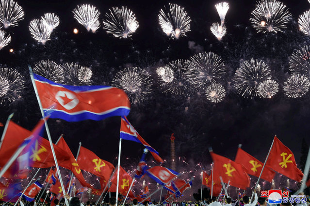 People wave North Korean flags beneathe a fireworks display during commemorations of the 75th anniversary of the founding of the ruling Workers' Party of Korea (WPK), in Pyongyang, North Korea in this image released by North Korea's Central News Agency on October 10, 2020. (Photo by KCNA via Reuters)