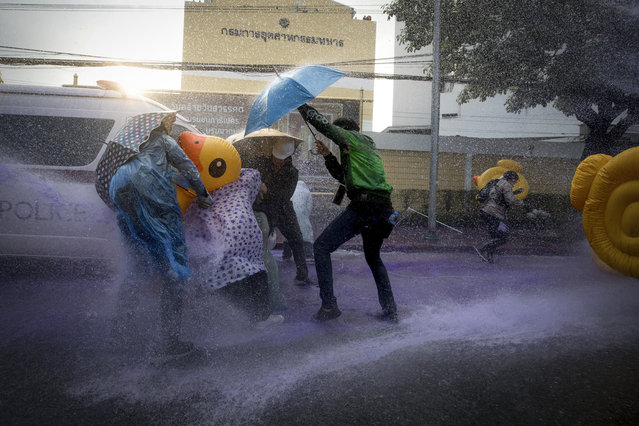 Pro-democracy protesters take cover with inflatable ducks and umbrellas as police fire water cannons during an anti-government rally near the Parliament in Bangkok, Tuesday, November 17, 2020. Thailand's political battleground shifted to the country's Parliament Tuesday, where lawmakers are considering proposals to amend the country's constitution, one of the core demands of the student-led pro-democracy movement. (Photo by Wason Wanichakorn/AP Photo)