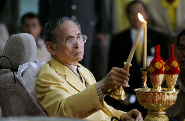 Thai King Bhumibol Adulyadej lights a candle in honour of his his father, Prince Mahidol Adulyadej, before his departure from Siriraj Hospital in Bangkok August 4, 2006. (Photo by Chaiwat Subprasom/Reuters)