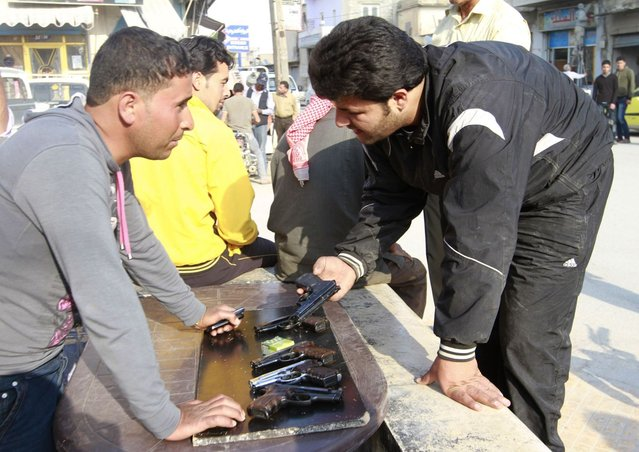 People sell hand guns on a street in the Syrian town of Tel Abyad April 23, 2013. Picture taken April 23, 2013. (Photo by Hamid Khatib/Reuters)
