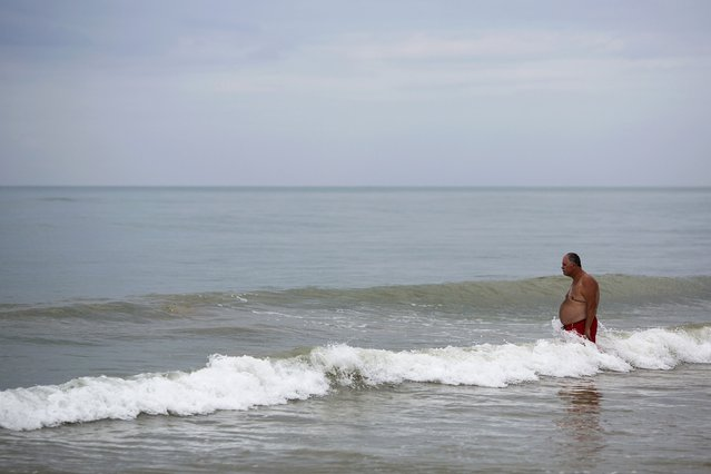 A tourist enters the ocean in Khao Lak, Phang Nga province December 15, 2014. Thailand prepares to mark the tenth anniversary of the 2004 tsunami, the deadliest on the record, that killed at least 226,000 people in 13 Asian and African countries. In Thailand, over 5300 people were killed, including several thousand foreign tourists, when the waves swamped six coastal provinces, turning some of the world's most beautiful beaches into mass graves. (Photo by Damir Sagolj/Reuters)