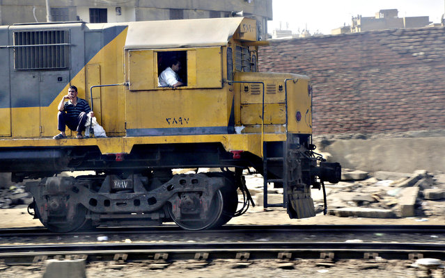 An Egyptian passenger sits on the locomotive of a train as it leaves Cairo train station in Egypt, Wednesday, October 14, 2015. (Photo by Amr Nabil/AP Photo)