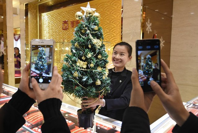 An employee poses for photographs with a Christmas tree decorated with gold accessories, as a promotional campaign of a gold store ahead of the Christmas, in Taiyuan, Shanxi province, China December 22, 2014. According to the store, about two kilograms (4.4 lbs) of gold accessories were used to decorate the tree. (Photo by Jon Woo/Reuters)