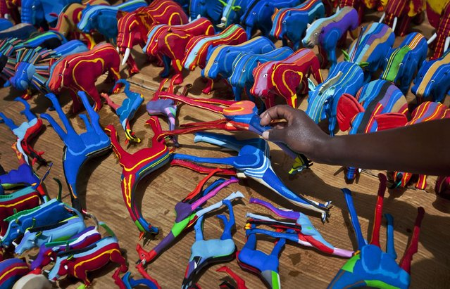 In this photo taken Monday, April 29, 2013, finished toy animals made from pieces of discarded flip-flops are laid out in rows to dry in the sun, having just been washed, at the Ocean Sole flip-flop recycling company in Nairobi, Kenya. The company is cleaning the East African country's beaches of used, washed-up flip-flops and the dirty pieces of rubber that were once cruising the Indian Ocean's currents are now being turned into colorful handmade giraffes, elephants and other toy animals. (Photo by Ben Curtis/AP Photo)