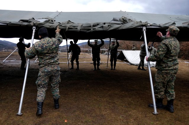 Bosnian soldiers put up the tents at the Lipa camp outside Bihac, Bosnia, Friday, January 1, 2021. The Bosnian army on Friday were setting up tents for hundreds of migrants who have been stuck in a burnt out camp in the northwest of the country in winter weather and with no facilities. Bosnia has faced international criticism leaving some 1,000 migrants practically without shelter after fire engulfed the Lipa camp near the border with Croatia last month. (Photo by Kemal Softic/AP Photo)