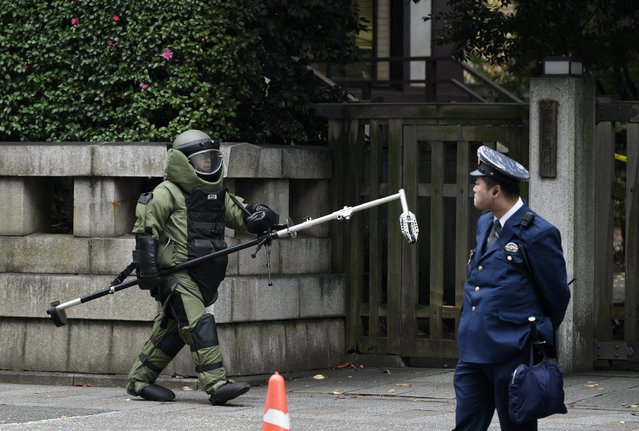 A bomb squad member wearing heavy equipment leaves the explosion site at the Yasukuni shrine precints in Tokyo, Japan, 23 November 2015. More than 100 police, firefighters and officials gathered at the site after an explosion was heard in the toilets of the Yasukuni Shrine, a controversial war shrine in the capital Tokyo. Local media reports said police found possible traces of an explosion, as well as batteries and wires at the shrine. There were no reports of injuries. (Photo by Franck Robichon/EPA)