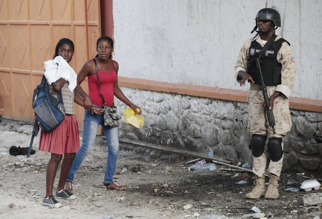 Two women walks past a National Police officer as he secures the area during a demonstration against the preliminary results of the presidential elections in Port-au-Prince, Haiti, November 20, 2015. (Photo by Andres Martinez Casares/Reuters)