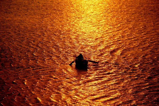 A man rows his boat on waters bathed in gold at sunset in Hyderabad, Pakistan, 30 December 2020. (Photo by Nadeem Khawar/EPA/EFE)