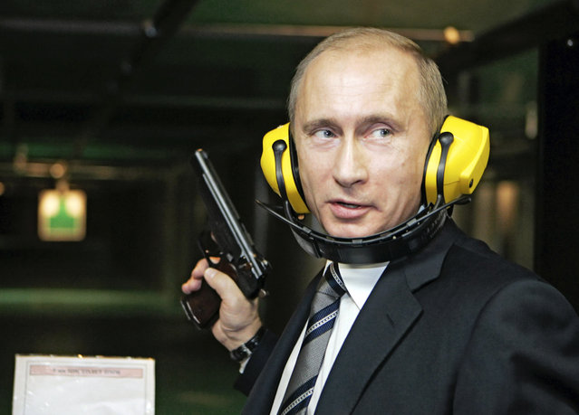 Vladimir Putin stands with a gun at a shooting gallery of the new GRU military intelligence headquarters building as he visits it in Moscow November 8, 2006. (Photo by Reuters/ITAR-TASS/Presidential Press Service)