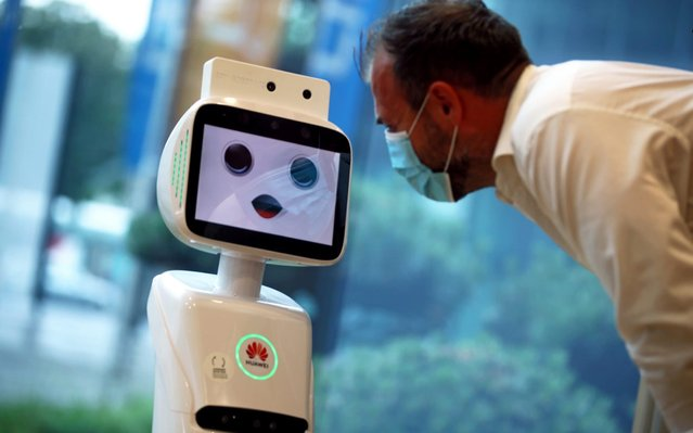 A 5G-robot, that is able to measure the temperature of a person and controls wether a face mask is being worn, speaks to an employee, following the coronavirus disease (COVID-19) outbreak in Linz, Austria, June 9, 2020. (Photo by Lisi Niesner/Reuters)