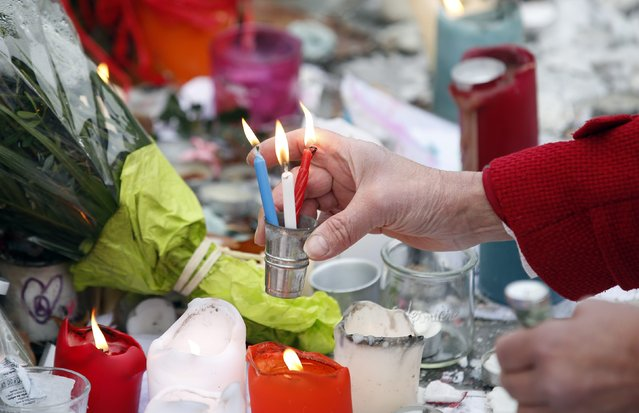 A woman installs blue, white and red candles, the colours of the French flag, during a tribute to the victims of Paris attacks, at the Place de la Republique in Paris, France, November 27, 2015 as the French President called on all French citizens to hang the tricolour national flag from their windows on Friday to pay tribute to the victims of the Paris attacks during a national day of homage. (Photo by Eric Gaillard/Reuters)