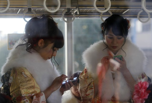 Japanese women in kimonos use smart phones inside a train after a Coming of Age Day celebration ceremony at an amusement park in Tokyo January 12, 2015. (Photo by Yuya Shino/Reuters)