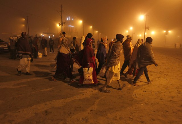 Hindu devotees arrive to take a holy dip at Sangam amid fog during the Magh Mela festival, on an early winter morning in the northern Indian city of Allahabad January 15, 2015. (Photo by Jitendra Prakash/Reuters)