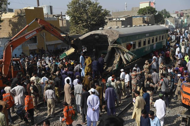 Pakistani bystanders watch the rescue work at the site of a collision between two trains in Karachi on November 3, 2016. At least 17 people have been killed and dozens more injured after two trains carrying hundreds of passengers collided in Pakistan's southern port city of Karachi, officials said. (Photo by Rizwan Tabassum/AFP Photo)