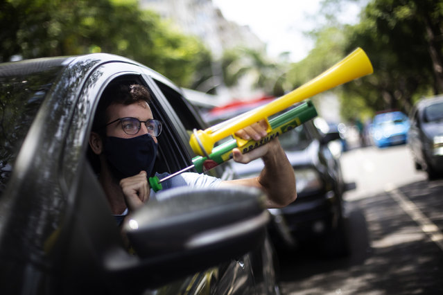 """A demonstrator shouts """"Out Bolsonaro"""" while using a noisemaker during a caravan to protest the government's handling of the COVID-19 pandemic and demand the impeachment of Brazilian President Jair Bolsonaro in Rio de Janeiro, Brazil, Saturday, Januyary 23, 2021. (Photo by Bruna Prado/AP Photo)"""